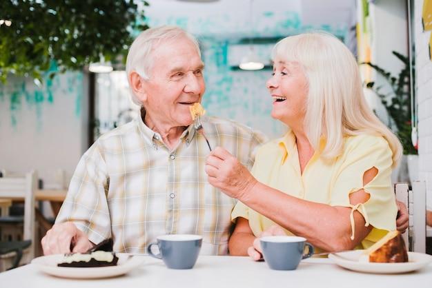 Romántica pareja senior disfrutando el postre en la cafetería