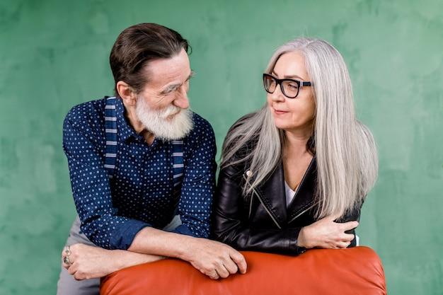 Romántica pareja senior, posando en elegante habitación sobre fondo de pared verde
