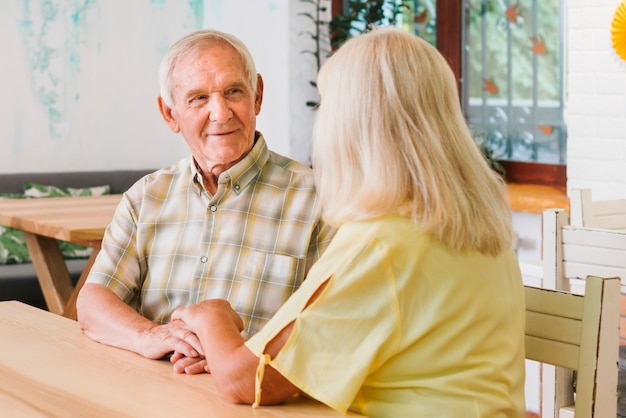 Romántica pareja senior sentado en la cafetería y cogidos de la mano