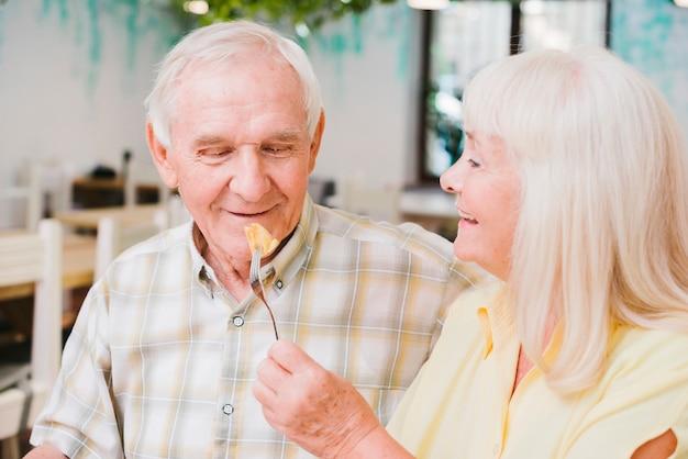 Romántica pareja senior sentado en la cafetería y disfrutando de pastel