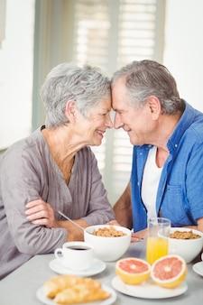 Romántica pareja senior sentado en la mesa