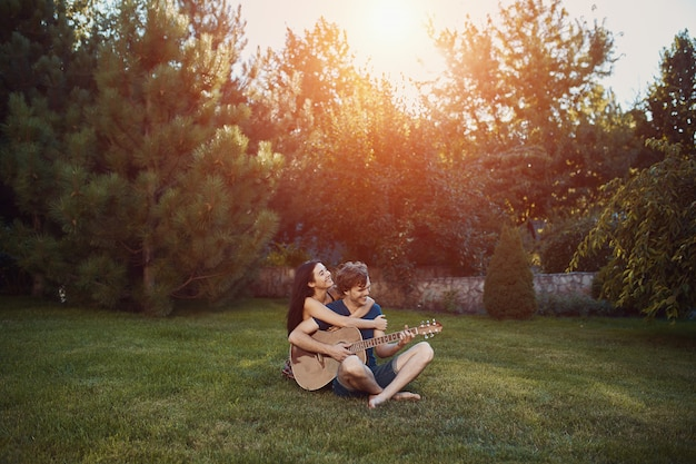 Romántica pareja sentada en el césped en el jardín