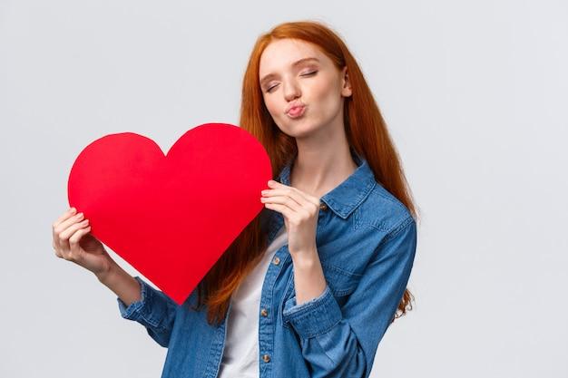 Romántica y soñadora linda pelirroja adolescente soñando con darle a su novio una gran tarjeta de corazón rojo para mostrar su afecto y amor, celebrar el día de san valentín con su pareja amada, de pie en la pared blanca