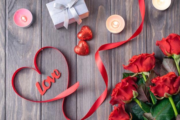 Romántica tarjeta de fondo de madera de san valentín con ramo de hermosas rosas rojas y letras de amor