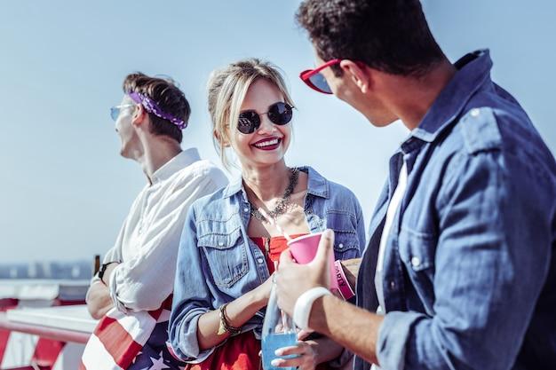 Romántico en el aire. mujer bonita rubia expresando positividad mientras mira a su amiga