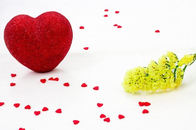Romántico corazón rojo brillante, flor amarilla y muchos pequeños corazones de azúcar en un blanco
