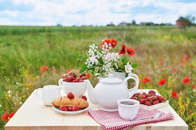 Romántico desayuno francés o rural de san valentín: té, fresas, cruasanes en la mesa en el campo de amapolas. campo y acogedor buenos días concepto de fin de semana.