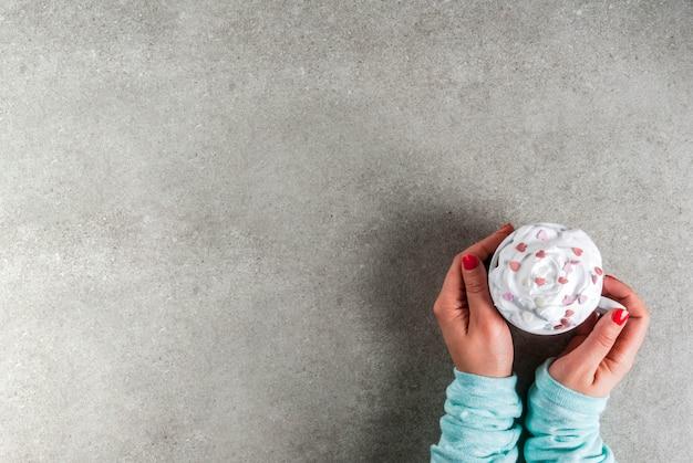 Romántico, el día de san valentín. chica bebiendo chocolate caliente con crema batida y corazones dulces, manos en la imagen, vista superior,
