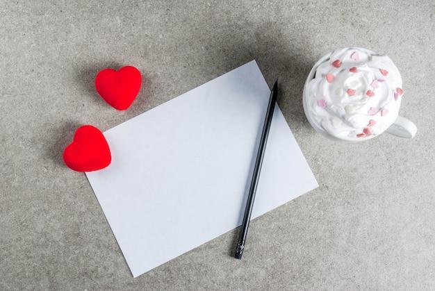 Romántico, el día de san valentín. mesa de piedra con papel en blanco para carta, felicitaciones, chocolate caliente con crema batida y corazones dulces, vista superior