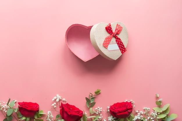 Romántico fondo rosa con flores rosas rojas y caja de regalo con forma de corazón