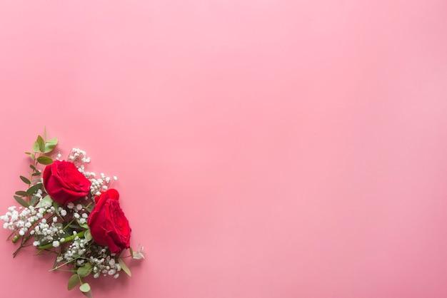 Romántico fondo rosa con rosas rojas y flores.