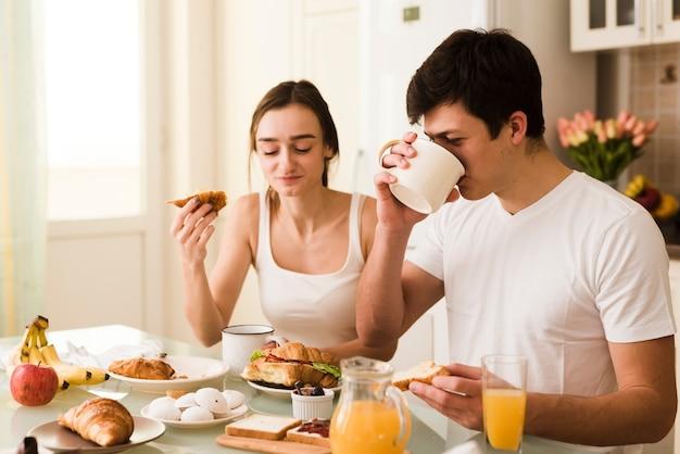 Romántico joven hombre y mujer que sirve el desayuno