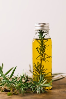 Romero en tiro vertical de botella de aceite de oliva