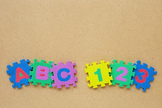 Rompecabezas del alfabeto con rompecabezas del número en de madera.