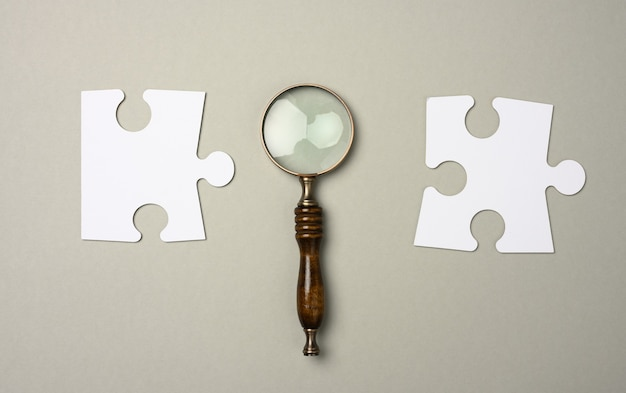 Rompecabezas alrededor de una lupa sobre un fondo gris. concepto de búsqueda de personas con talento, contratación de personal, solución al problema