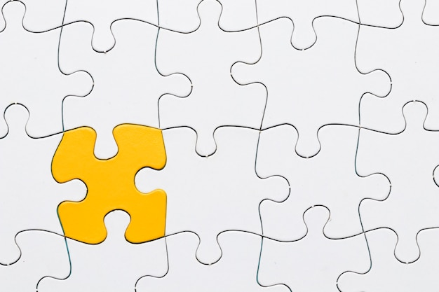 Rompecabezas amarillo entre rompecabezas blanco rejilla