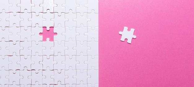 Rompecabezas blanco sobre fondo rosa. pieza perdida.