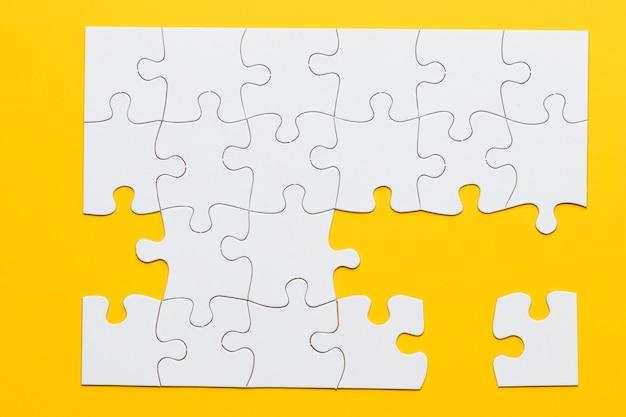Rompecabezas de cartón blanco sobre fondo amarillo
