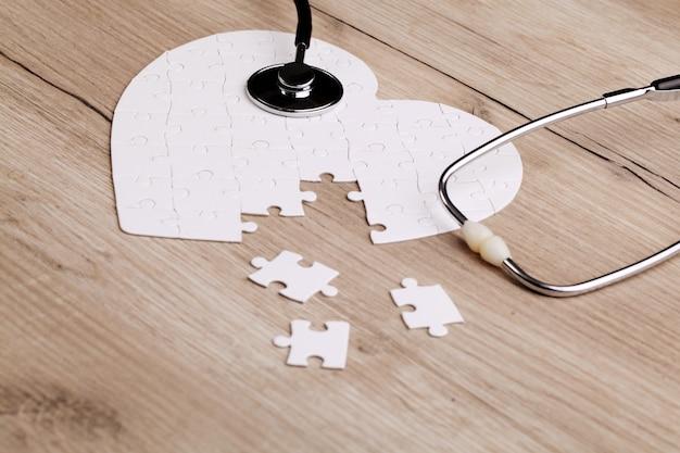 Rompecabezas en forma de corazón blanco con estetoscopio