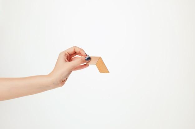 El rompecabezas de madera de juguete en mano aislado en la pared blanca