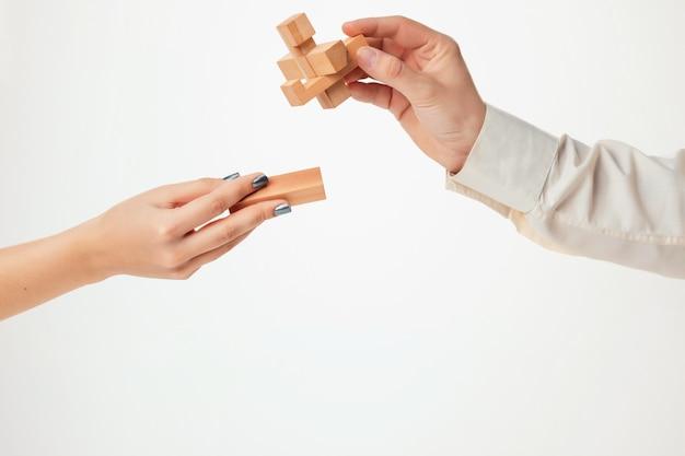 El rompecabezas de madera de juguete en manos aisladas en la pared blanca