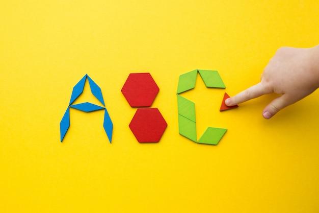 El rompecabezas de madera del tangram de color en forma de letras del alfabeto abc sobre fondo amarillo con la mano de un niño