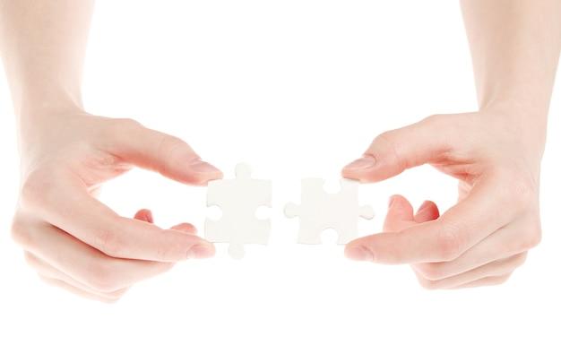 Rompecabezas en mano aislado en pared blanca