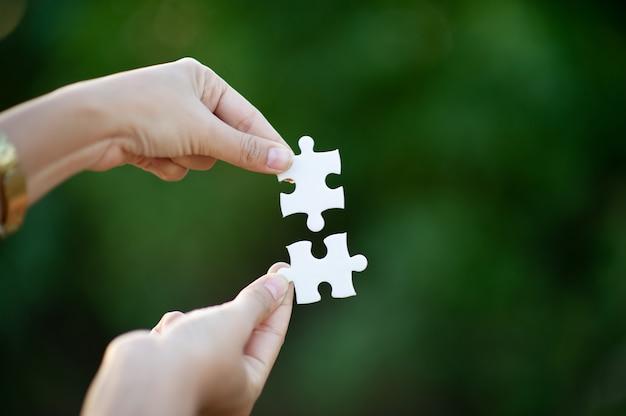Rompecabezas de manos y blanco imagen de primer plano e integración concepto de negocio y unidad