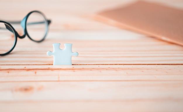Un rompecabezas en la mesa de madera con lentes borrosas y cuaderno marrón, solución para el concepto de éxito