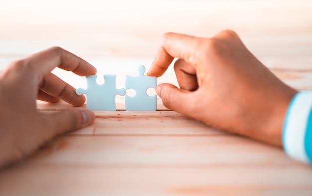 Rompecabezas que conecta a dos manos, solución al concepto de éxito.