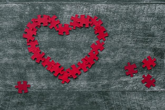 Rompecabezas rojo corazón en la mesa de madera oscura, vista superior