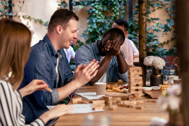 Rompiendo la torre jenga y riéndose con los mejores amigos en el acogedor restaurante al aire libre