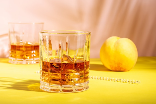 Ron o amaretto amargo con hielo en un vaso sobre un fondo brillante.