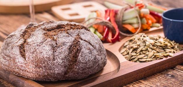 Ronda fresca de pan oscuro en un plato de madera