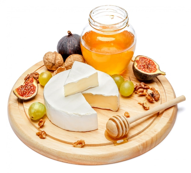 Ronda de queso brie o queso camembert en tabla de cortar mesa blanca