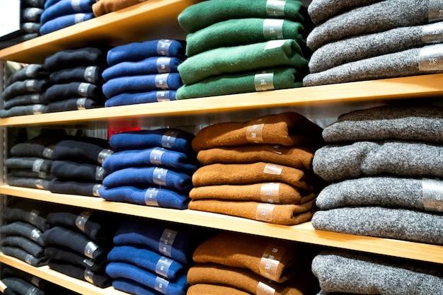 Ropa abrigada cuidadosamente doblada en un estante. una fila de jerséis, cárdigans, sudaderas, suéteres, sudaderas con capucha de colores en la sala de exposiciones o en la tienda.