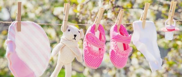 La ropa y los accesorios del bebé pesan sobre la cuerda después de lavarse al aire libre.