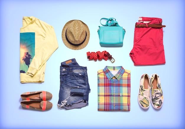 Ropa y accesorios. colección de ropa de verano. ropa doblada de colores sobre fondo azul.