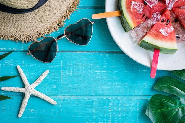 Ropa con accesorios y frutas tropicales y flores sobre fondo blanco de madera en verano.