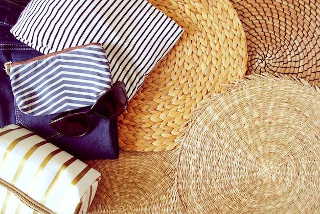 Ropa y accesorios de verano de mujer sobre fondo de mantel de mimbre, vista superior.