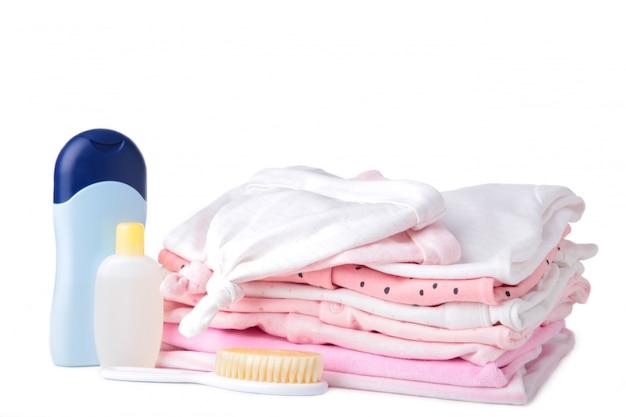 Ropa de bebé con accesorios de ducha aislado sobre fondo blanco.