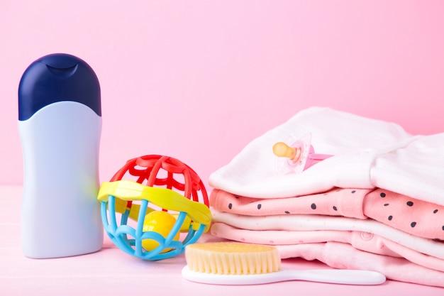 Ropa de bebé con accesorios de ducha sobre un fondo rosa