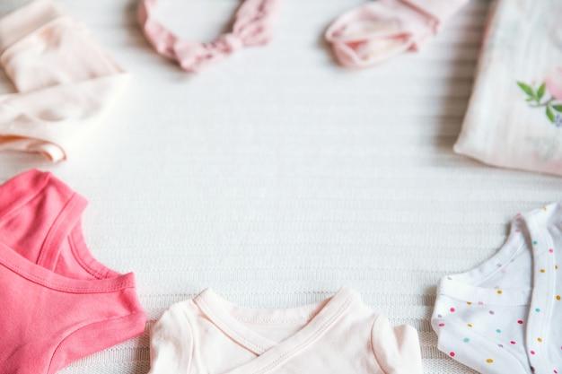 Ropa de bebé y artículos de primera necesidad sobre un fondo de tela ligera. ambiente suave y acogedor.