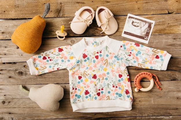 Ropa de bebé floral con zapatos; chupete; cuadro ecográfico y peluche en mesa de madera.