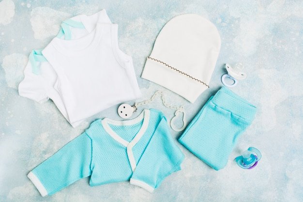 Ropa de bebé recién nacido: mono blanco, camisa azul, pantalón azul, sombrero blanco y pacifie