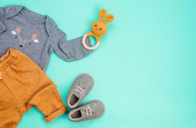 Ropa de bebé recién nacido y puf de conejo en turquesa