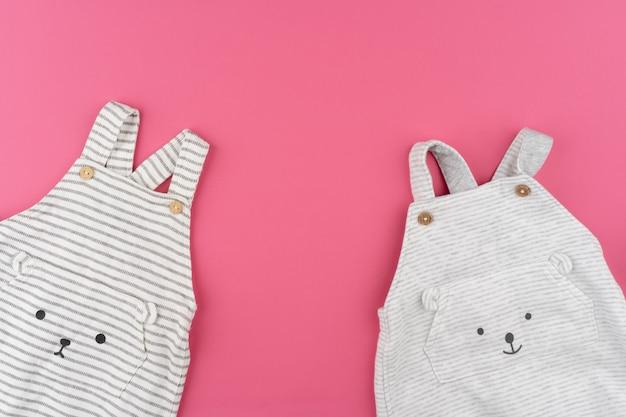 Ropa de bebé en vista superior de fondo rosa