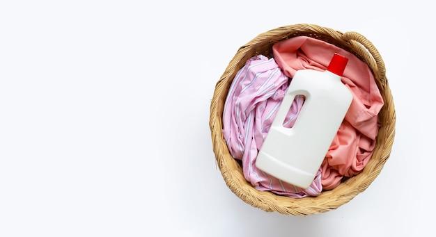 Ropa con botella de plástico de detergente en canasta de lavandería sobre fondo blanco. copia espacio