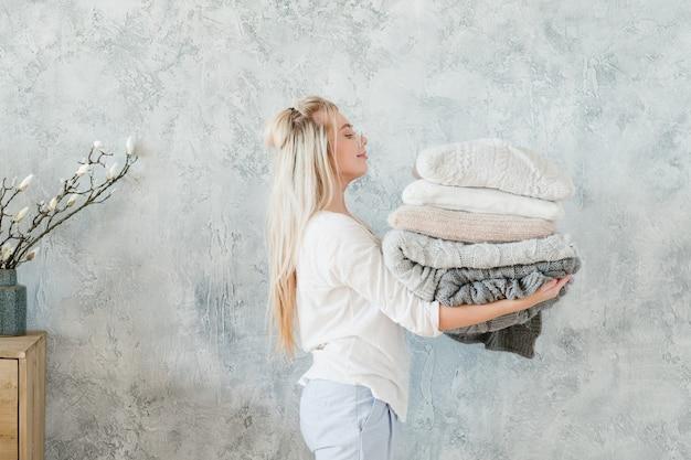 Ropa de cama acogedora para el invierno. ama de casa feliz con pila de almohada y manta de punto caliente.