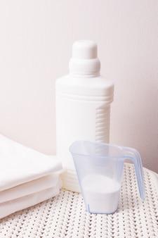 Ropa de cama blanca, lejía líquida y detergente en polvo en una taza medidora en la canasta de ropa sucia